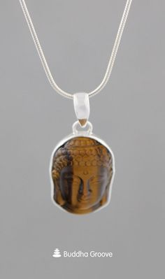 This Buddha face pendant is made of Tiger's Eye stone, a gemstone of strength, willpower, and luck. Tiger's Eye is set in a sterling silver base. Buddha Jewelry, Buddha Face, Tigers Eye Gemstone, Eye Stone, Willpower, Strength, Calm, Pendants, Pendant Necklace