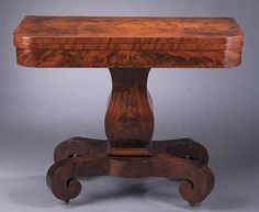 """An American Labeled Late Classical Mahogany Games Table, c. 1829-1835, New York, bearing paper label """"MEEKS & SONS MANUFACTORY/OF/CABINET FURNITURE/ JOSEPH MEEKS & SONS/ Nos. 43 & 45 BROAD STREET/NEW YORK"""" , New York, the fold-over top with rounded corners above a finely veneered and banded apron, raised on a flared pedestal connected to a raised plinth with scrolled legs fitted with casters, height 28 3/8 in., width 36 in., depth 35 1/2 in. Provenance: High Museum, Atlanta"""