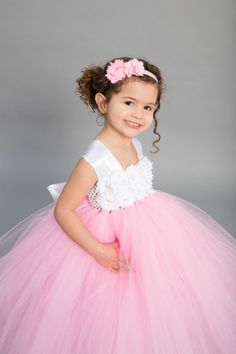 Make your wedding stand out with this beautiful White and Pink Flower Girl Dress. This multilayer dress is made with yards and yards of premium soft tulle. Embellished with white flowers featuring rhinestone encased faux pearls. The double white satin straps lay over the shoulders and tie in the back into one large bow.  The listed length is for a measurement from armpit to hem.  **Please measure from underneath the armpit to the floor or top of foot.**  Each dress is handmade as ordered…