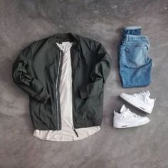 olive bomber. long off-white / tan tee. light wash denim. all white sneakers.