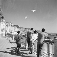 UFO:Sicily, Italy (December 1954)  Four Sicilians gaze skyward at two unidentified objects similar to those being mentioned in press reports and appearing in photos from other European countries. The authenticity of the images was checked by questioning the photographer, who said the objects were in the sky and remained still for several minutes.