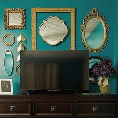 A beautiful gold mirror and gold frame gallery wall behind a tv on a dresser in a teal master bedroom.
