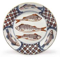 AN ENGLISH DELFT POLYCHROME PLATE CIRCA 1775, PROBABLY BRISTOL Painted in manganese, iron-red and blue, the center with three fish, the border with three further fish reserved by trellis