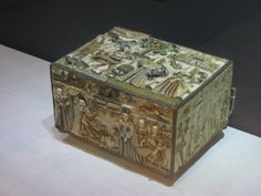 The embroidery on this type of box was made by young girls. The raised figures are padded and parts of their costumes, flowers and curtains in lace stitches, are stiffened with wire and stand free from the surface. The biblical scene on the front represents King Solomon and the Queen of Sheba