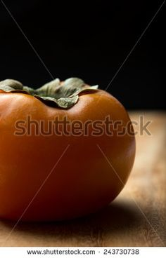 fresh, ripe persimmon, isolated on a table, black background, closeup, vertical. - stock photo