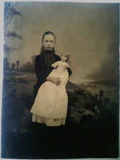 Girl with a doll with a long white dress