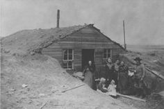 In this undated photograph, the L.A. Mead family stands outside their dugout located near Bloom, Ford County, Kansas. Dugouts such as this, as well as sod houses, were common dwelling places on the high plains of Kansas due to the lack of wood and other natural resources. This family was fortunate enough to have glass windows, wood siding, and a stovepipe; these amenities would have been considered luxuries by many pioneers out west.