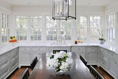 Kitchen with only lower white cabinets, bank of windows wood floors