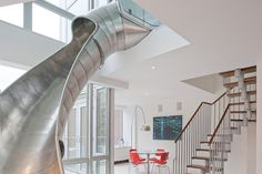 Tasked with connecting two separate apartments in New York's East Village, Turett Collaborative Architects sought inspiration on the playground. A helical slide winds down from the second-floor office into the living room through a double-height atrium, offering nonpareil views of the city skyline.
