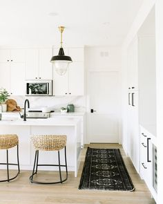 black and white kitchen with woven bar stools