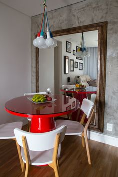Concrete on wall + lighting  Colored wire + big mirror to enlarge the small space + bright  color table = creative affordable decor ideas ( Pfoto : Vanessa Volk / Via Pe Direito Arquitetura)
