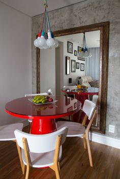 Sala de jantar com parede pintada com tinta que imita cimento queimado e espelho para dar mais amplitude. A cor fica por conta da mesa vermelha e da luminária