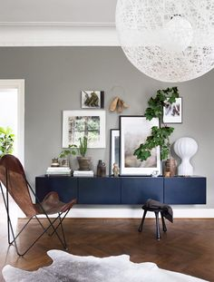 Väggförvaringen är Ikeas Bestå som omlackerats i samma mörkblå ton som köket. Uttrycket ovanpå är i ständig förnyelse. Här samlas stilleben som ofta talar om vilken årstid vi befinner oss i. Bordslampa Gatto, från Flos. Taklampa Random Light, Moooi.