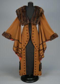 * WOOL COAT with APPLIQUE and FUR TRIM, EARLY 20th C. Light brown with exaggerated wizard sleeve appliqued in darker brown with black silk tassels, fur collar and cuff, contrasting faux button trim and satin lining
