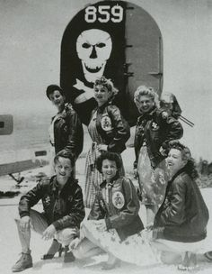 """USO girls wear jackets belonging to the Bomb Group, aka """"Jolly Rogers"""" under a bomber WWII"""