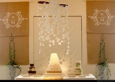 Wedding cake display with burlap monogrammed curtains and hanging decorations