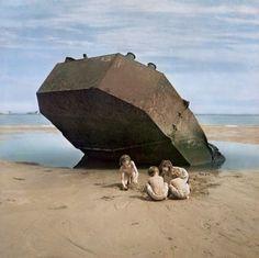 David Seymour  Children playing in front of sunken World War II boat  Omaha Beach, Normandy, France 1947