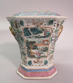A hexagonal Chinese famille rose porcelain flower vase late qing dynasty mounted by two gilt rope twist handles, decorated to body with four panels depicting figures in mountainous landscape, lid with five aperture within lingzhi band rim. H: 9 in., 22.9 cm