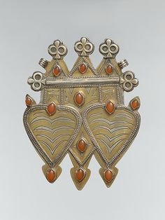 Central Asia or Iran | Pectoral ornament; Silver, fire-gilded and chased, with decorative wire and stamping, ram's-head terminals, and cabochon carnelians | 20th century