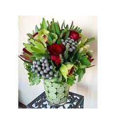This exquisite arrangement with red roses, orchids and limes is populated with unique greens and berries.