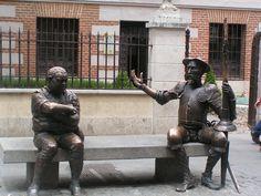 Justo antes de entrar en la Casa de Cervantes de Alcalá de Henarés (a tan solo 23 km. De Madrid capital), en plena Calle Mayor, te encontrarás con esta simpatiquísima estatua de Don Quijote y Sancho Panza que te dan la bienvenida y te invitan a que te sientes con ellos y te hagas una foto. ¡Aviso!: Es foto obligada para visitantes a Alcalá, sin duda. Será por ese brazo alzado de Don Quijote, que parece decirte: Vente aquí, forastero, y siéntate a mi lado en actitud de darte una palmadita en…