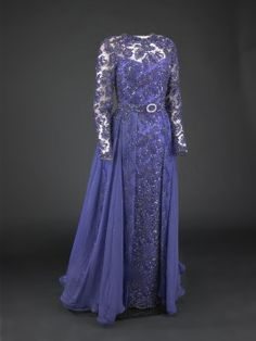 """Hillary Clinton hasn't always gotten rave reviews when it comes to her fashion choices. During inaugural week in 1993, she made a particularly unpopular decision about a hat. But the purple dress she chose for the inaugural ball was wellreceived. """"Sarah Phillips, until now a little-known New York designer, is responsible for the blue violet lace dress with the mousseline overskirt that won thumbs-up reviews from just about everyone who saw it,"""" wrote the New YorkTimes. Like it or not…"""