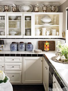 Designers and owners Craig Schumacher and Philip Kirk avoided an extensive kitchen remodel by painting existing cabinets Benjamin Moore Brilliant White and installing inexpensive black and white tile on counters and backsplashes.