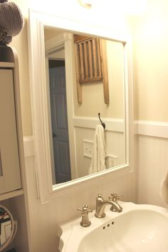 Frame a small bathroom mirror with trim and adhesive caulk to make it look like a piece of art.