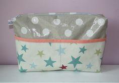 Wunderschöne Kosmetiktasche/Waschtasche aus beigen/weißen Wachstuch mit Sternen und Punkten. Gefüttert mit blauem Baumwollstoff mit weißen Punkten. Zwei Eingrifftaschen draußen und ein großes Reißverschlussfach.  Höhe 16,5 cm, Breite 25,5 cm, Tiefe 6 cm