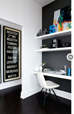 The wall is painted with matt charcoal color which goes well with glossy white shelves.