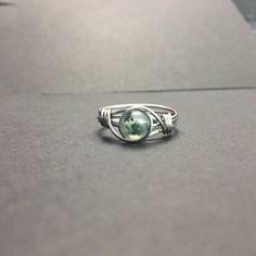 Moss agate ring, hand wrapped in stainless steel. I used stainless steel to wire wrap the stone. Stainless steel is by far the best jewelry metal. It tarnishes slower than silver, is stronger than gold, and doesnt turn your skin green like copper.   Multiple ring purchasing discount: Enter the coupon code MULTIRING at checkout to pay only $5 a ring when buying multiple rings.   Matching necklace: https://www.etsy.com/listing/498393762/tiny-moss-agate-charm-necklace?re...