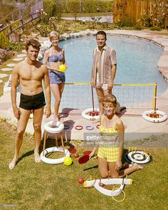 American actor Clint Eastwood (left) with his wife, Maggie (foreground), and friends by a swimming pool, circa 1960.