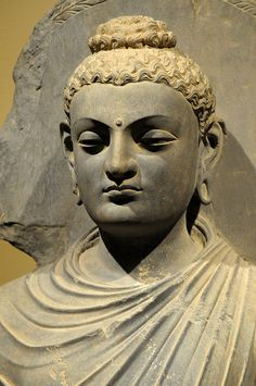 Buddha with a topknot. Gandhara was the region that lies between N.W  Pakistan and E. Afghanistan. first mentioned in a text in the 9th C. BCE. Over the next 900 years the region was conquered by Alexander the Great, the Indian Mauryan dynasty, the Parthians, the Indo-Greeks, and finally the Central Asian Kushan Empire. This complex history, with its many cultural influences, formed the foundation for a region where Buddhism flourished and the basis for some of the earlier images of Buddha.