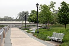 Robert C. Beutter Riverfront Park | Rundell Ernstberger Associates helped transform & revitalize an abandoned industrial site along the St. Joseph River in Mishawaka, IN into a 5.5-acre park & public gathering space. The design embraced a historic canal by featuring a race with decorative weirs, public-commissioned artwork, flood-prone plantings, & two metal pedestrian bridges that span the river to provide a pleasant circular trail system. Photo by REA.