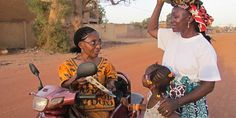 While on her three-wheeled motor scooter, Sarah Maiga preaches to a woman and a little girl