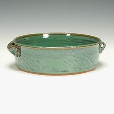 """Stoneware baking dish with handles. Wheel thrown stoneware baking dish/ casserole with handles. Copper green glaze. The image is representative of the piece for sale and variations in form and color may occur. Lead-free, oven, microwave and dishwasher safe. Signed on the bottom by the artist. Approximately 2"""" high x 8"""" diameter. Ready to ship."""
