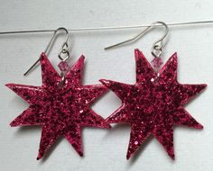 These Jem inspired earrings measure approximately 1 3/4 from the top of the silver tone fish hook to the bottom of the star. Rose pink Swarovski crystals add extra sparkle to the earrings. The 1 1/2 emblem is made of layers of sealed paper with hot pink glitter on the front and back. These earrings are water resistant, but not water proof. Theyve been field tested in light to medium rain, but I would not recommend swimming with them.