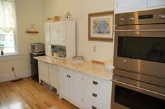 Kitchen:Charming Kitchen Remodeling For Small Kitchen With Stainless Steel Ovens Also White Kitchen Cabinets Also Abastract Painting Also Marble Bowl Also Books Also Curtains As Well As Laminate Floor Kitchen Remodeling Makes Solution for Small Kitchens