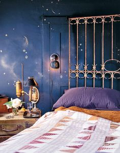 This night sky wall effect was created by mixing black paint with dark navy. Shadows and clouds were then brushed on, followed by gold and silver metallic stars. A stack of vintage suitcases is used for out-of season storage and doubles as a bedside table. An old garden gate makes a unique headboard.