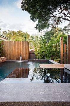 Elegante y moderno diseño de patio trasero para el disfrute al aire libre de una familia en Melbourne (Australia). Con piso de madera, piscina desbordante ejecutada en vaso de hormigón armado, barbacoa de obra, y una estupenda iluminación oculta. De COS Design y otros 3 equipos colaboradores.