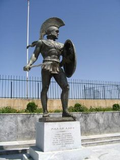 Statue of Leonidas   Ancient Greek Military Dress  Geaves: Like shin guards; Helmet: metal; Cuirass: armor piece that fits torso and looks like abs.  Found on: tripadvisor.com Original Source: Leonidas Statue at the monument of Thermopylae.