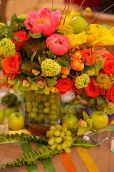 Grapes in a vase of flowers love it saw the oranges lemons and limes even apples but GRAPES my fav