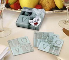 """These four love glass coasters come in a clear box with a white bow and a thank you tag attached. This item measures 3 1/2"""" by 3 1/2"""". Declare your love with these playfully designed glass LOVE coasters! Lovely as bridal shower favors or for any occasion, your guests will adore these fun and functional home accessories. Each made of tempered glass for extra strength, these bridal shower favors come festively packaged in a clear box tied with a bow. Each set of four glass L..."""