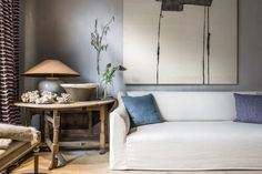 Breathtaking Belgian style design by Natalie Haegeman in her NH Interiors showroom with Belgian linen sofa, contemporary abstract painting, rustic wood side table and lamp, plaster walls and warm wood floors.