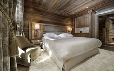 architecture white bed on white furry rug near brown sofa in front of glass window luxurious wooden chalet interior design in courchevel the french alps