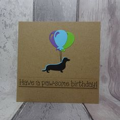 Sausage dog birthday card with a Dashchund holding a bunch of birthday balloons.  This handmade birthday balloons card has a silhouette of a Sausage Dog standing happily, holding the strings to a bunch of balloons. The sentiment on this handmade birthday card is added with 3D foam and reads: Have a paw-some birthday! PERSONALISING YOUR CARD: You can choose the colour of the balloons and matching dog shadow on this happy birthday card from the drop-down menu. If you choose a singular colour…