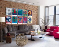 This urban penthouse loft is home to comedian Will Ferrell. Vivid poster prints are hung in a grid like formation above a large charcoal sectional. Simple furniture provides ample room to lounge around and take it all in. The bronze lamp, and heavy wood side tables couple with exposed brick creating an industrial quality in the space. Branches, vases, and glass decanters are the only evidence of decorative décor allowing ample space for Will's loud and dynamic personality. Neutral colors…