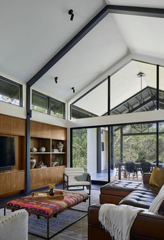 A light-filled living room with high ceilings and built-in cabinetry was added to the back of this modern house.