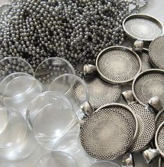 Need jewelry making supplies? 20 pieces of antiqued silver pendant trays with domed glass inserts. Includes 20 antique silver 24 inch ball chain necklaces.Appr
