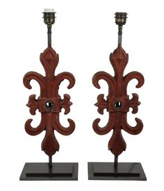 A pair of French wrought iron architectural elements, of fleur de lis design, mounted on to electrified bronze plinth stands, as a pair of table lamps. Measure: 60cm high x 20cm wide x 12cm deep   Stock Code ET02179